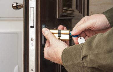 homeguide locksmith rekeying a front door lock on house
